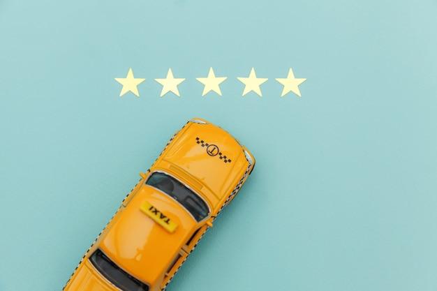 Carrozza di taxi gialla dell'automobile del giocattolo e una valutazione di 5 stelle isolata su fondo blu. applicazione per smartphone del servizio taxi per la ricerca online di chiamate e prenotazioni concetto di taxi. simbolo taxi. copia spazio.