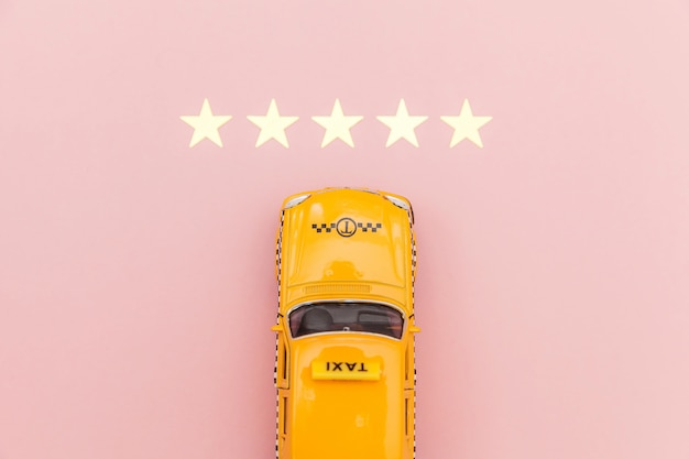 Carrozza di taxi gialla dell'automobile del giocattolo e una valutazione di 5 stelle isolata su fondo rosa. applicazione del telefono del servizio taxi per la ricerca online di chiamata e prenotazione concetto di cabina. simbolo taxi. copia spazio.