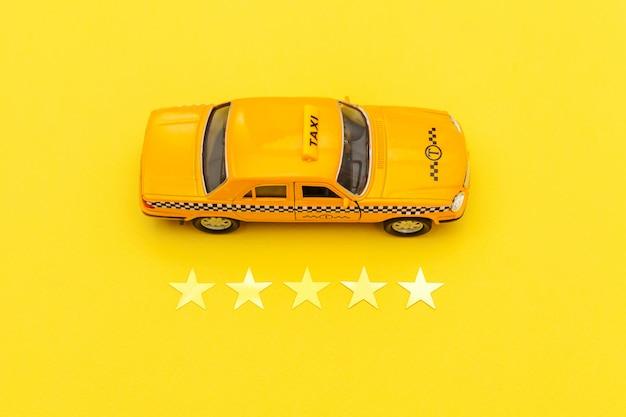 Carrozza di taxi gialla dell'automobile del giocattolo e una valutazione di 5 stelle isolata su fondo giallo. applicazione del telefono del servizio taxi per la ricerca online di chiamata e prenotazione concetto di cabina. simbolo taxi. copia spazio.