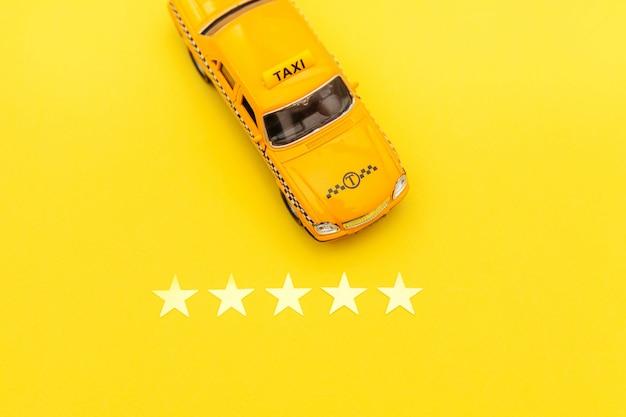 Carrozza di taxi gialla dell'automobile del giocattolo e una valutazione di 5 stelle isolata su fondo giallo