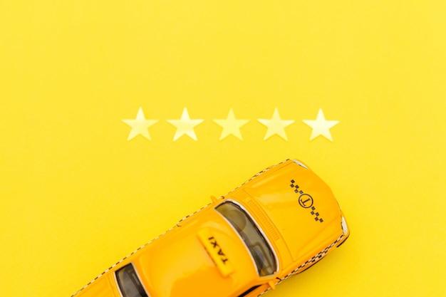 Carrozza di taxi gialla dell'automobile del giocattolo e una valutazione di 5 stelle isolata su giallo. applicazione per smartphone del servizio taxi per la ricerca online di chiamate e prenotazioni concetto di taxi. simbolo taxi. copia spazio.