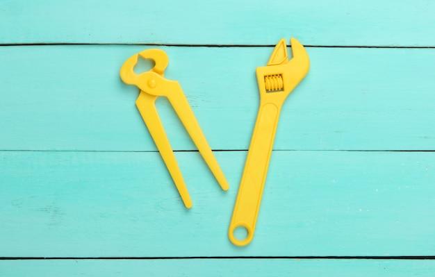 Chiave e pinze di plastica del giocattolo giallo su legno blu.