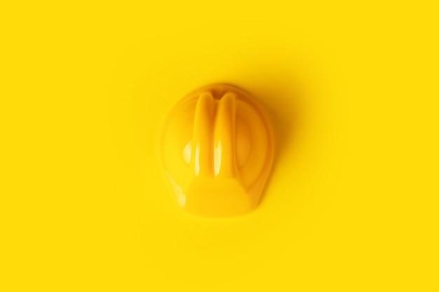 Casco del lavoratore giocattolo giallo su sfondo giallo, concetto di costruzione minimalista