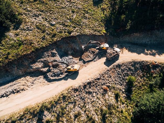 Il trattore cingolato giallo carica un veicolo da cava con vista sulla sabbia dal drone
