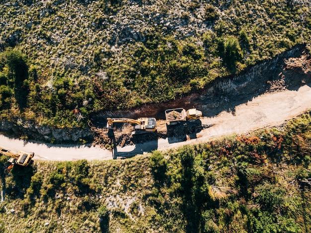 Il trattore cingolato giallo carica un veicolo da cava con vista sulla sabbia dall'alto