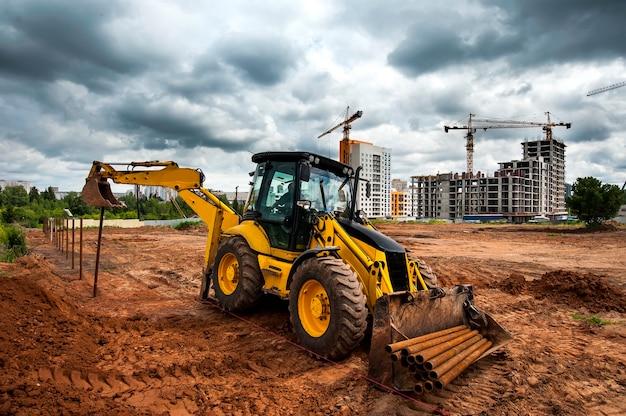 Il trattore giallo in un cantiere edile imposta i poli nel campo
