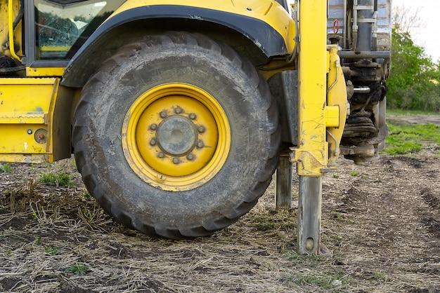 Trattore giallo sul campo in piedi sulle zampe posteriori.
