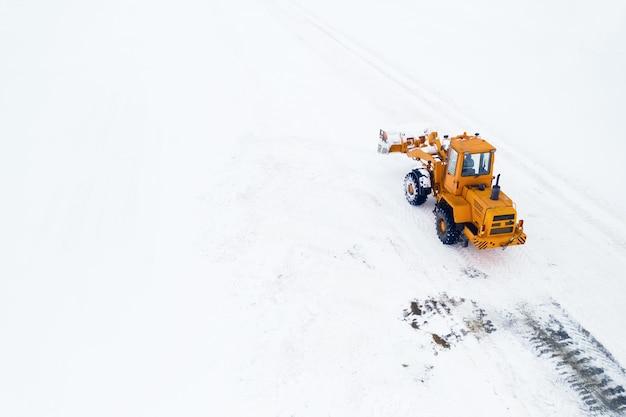 Il trattore giallo con un secchio rimuove la neve dalla vista superiore della strada.