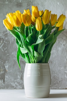 Bouquet di tulipani gialli in vaso bianco su sfondo grigio cemento. verticale