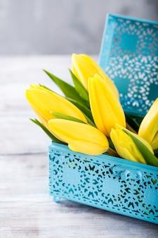 Tulipani gialli in una scatola di metallo blu sulla superficie grigio chiaro. un regalo per la festa della donna. biglietto di auguri per la festa della mamma. copia spazio