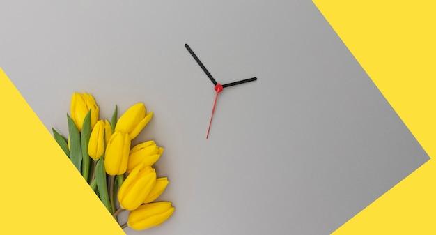 Tulipani gialli e lancette dell'orologio su uno sfondo giallo e grigio