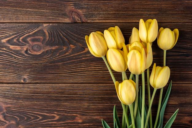 Tulipani gialli sulla tavola di legno scuro.