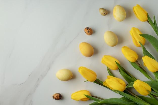 Tulipani gialli e uova di pasqua tinte naturalmente sulla tavola di marmo