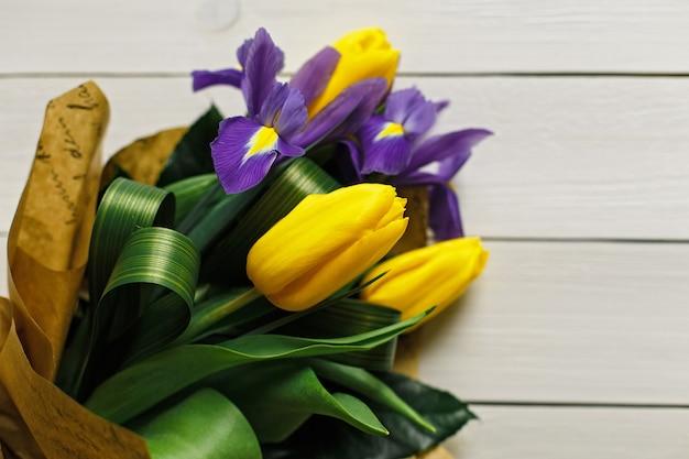 Tulipani gialli su un fondo di legno bianco