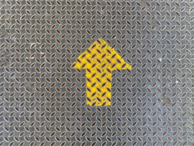 Segno di freccia di direzione in alto giallo sulla parete di piastra metallica