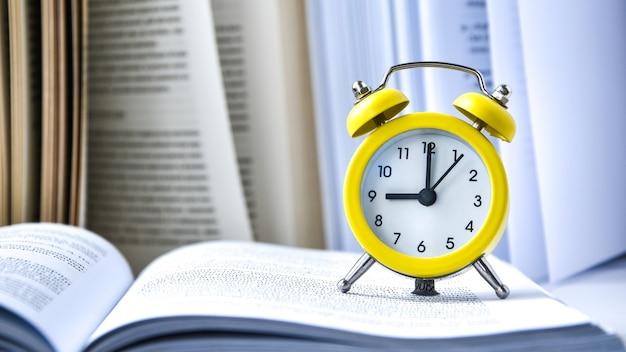 Sveglia vintage gialla con libro su sfondo bianco, ritorno a scuola, tempo per imparare, conoscenza della ricchezza, copia spazio per il testo