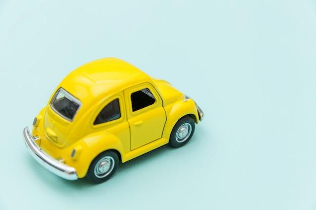 Retro automobile gialla d'annata del giocattolo isolata su fondo variopinto pastello blu