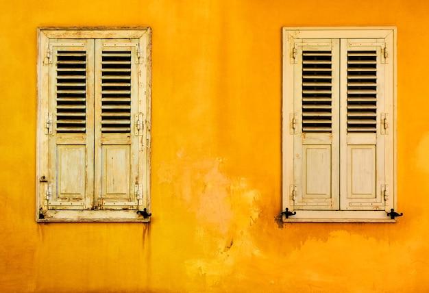 Muro giallo con due finestre con persiane nel quartiere di plaka ad atene, grecia