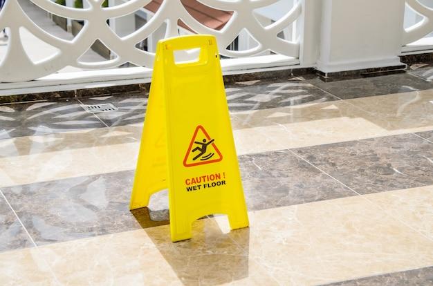 Segnale di avvertimento giallo attenzione pavimento bagnato su un pavimento di marmo in un'area pubblica.