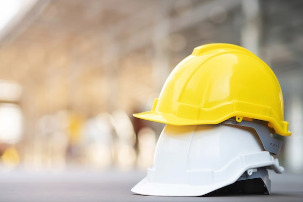 Cappello del casco di usura di sicurezza duro giallo e bianco nel progetto alla costruzione del sito sul pavimento di cemento con luce solare. casco per operaio come ingegnere o operaio. concetto di sicurezza prima di tutto.