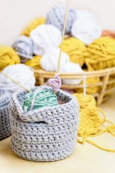 Gomitoli di cotone giallo, bianco, senape, grigio e cesto di maglia grigia