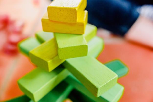 Blocchi di legno gialli in equilibrio in una torre giocattolo.
