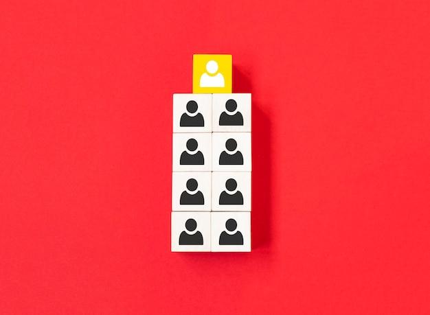 Il cubo di legno giallo con l'icona della persona si distingue dalla massa su sfondo blu. opinione dissenziente, punti di vista divergenti e concetti diversi