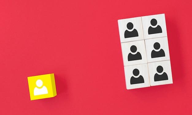 Il cubo di legno giallo con l'icona della persona si distingue dalla massa su sfondo blu