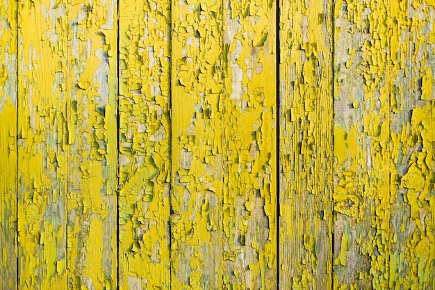 Staccionata in legno giallo con crepe e vecchia vernice.