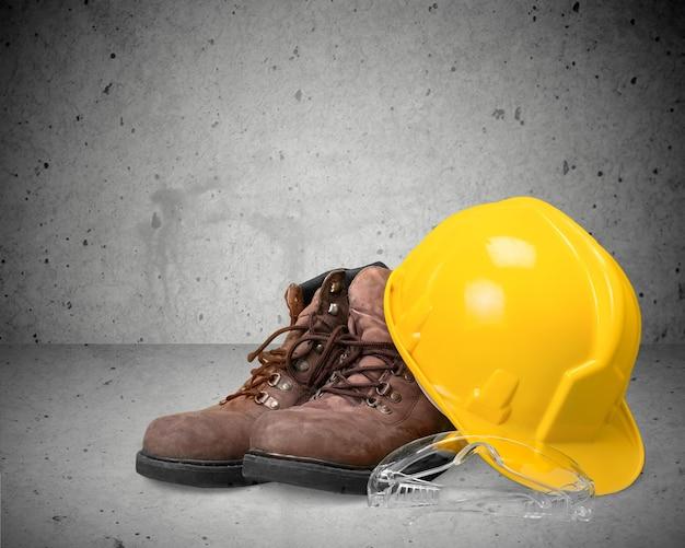 Cappello duro da lavoro giallo, occhiali e stivali da lavoro sullo sfondo