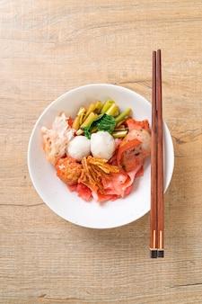 (yen-ta-four) - noodle secchi in stile tailandese con tofu assortiti e polpette di pesce in zuppa rossa - stile di cibo asiatico