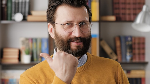 S gesto di emozione. eccitato gioioso uomo barbuto con gli occhiali in ufficio o nella stanza dell'appartamento che guarda l'obbiettivo e stringe emotivamente la mano nel pugno e mostra la sua soddisfazione e forse la vittoria