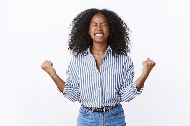 Sì, alla fine ce l'ha fatta. ritratto sollevato eccitato felice celebrante donna ha raggiunto il raggiungimento obiettivo successo stringendo i pugni gesto vittoria chiudere gli occhi sorridente grazie a dio vincere, in piedi muro bianco