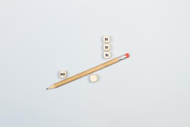 Sì e nessuna parola in cubi di legno spagnolo con una matita in modo equilibrato su uno sfondo grigio