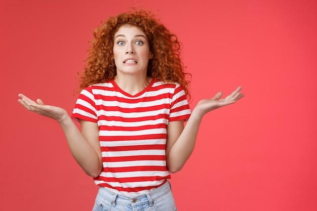 Oddio come faccio a saperlo. ignaro preoccupato imbarazzante carino rossa ragazza riccia stringere i denti sogghignando incerto panico non può rispondere occhi schioccanti confusi alzando le mani divaricate di lato piena incredulità.