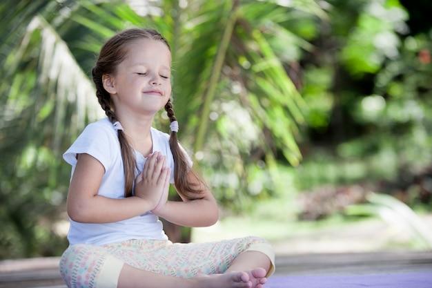 Bambino di yoga che fa esercizio sulla piattaforma di legno tra piante verdi all'aperto.