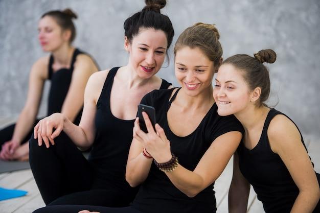 Lezione di yoga di allegri amici millenari la gente prende un selfie