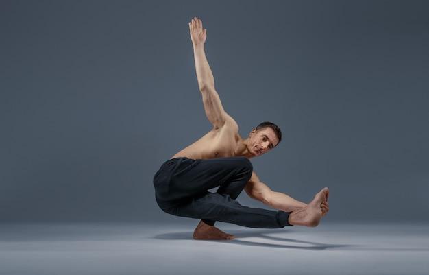 Yoga facendo esercizio di stretching in studio, muro grigio uomo forte che pratica yogi, allenamento asana, massima concentrazione, stile di vita sano