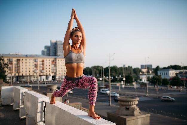 Yoga fitnes training, donna che medita, città. yogi allenamento all'aperto