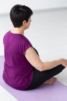Yoga, armonia, concetto di persone - donna di mezza età seduta nella posizione del loto, vista posteriore ravvicinata