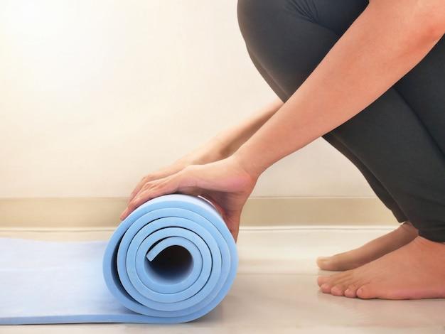 Stuoia di esercizio di rotolamento della donna di stile di vita attivo yoga a casa.