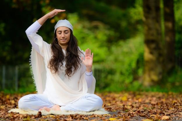 Istruttore di yoga pratica esercizi nel parco in autunno