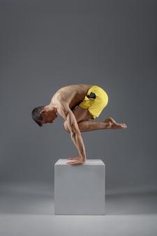 Lo yoga mantiene l'equilibrio sulle mani in una posa difficile sul piedistallo, posizione di meditazione, muro grigio uomo forte che fa esercizi yogi, allenamento asana, massima concentrazione, stile di vita sano