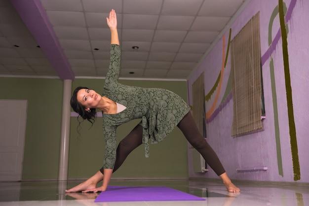 Studente di yoga che esegue yoga in una donna studio./yogi dimostrando asana yoga in classe di fitness.