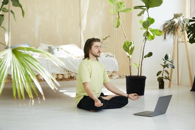 Uomo di yoga che fa pratica a casa con il computer portatile, concetto di meditazione attraverso il web utilizzando il computer portatile
