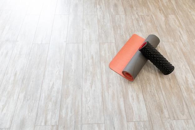 Tappetino da yoga e rullo di schiuma nel soggiorno per la meditazione yoga