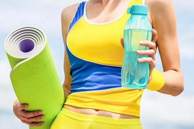 Tappetino da yoga e bottiglia d'acqua. concetto di stile di vita sano. avvicinamento. ragazza di forma fisica con la stuoia di yoga sopra il fondo del cielo. la donna in abbigliamento sportivo tiene in mano un tappetino da yoga e una bottiglia d'acqua.