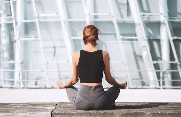 Yoga e meditazione in città vista posteriore della donna che medita e fa esercizi di respirazione all'esterno