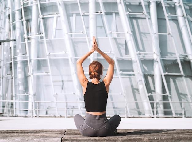 Yoga e meditazione nella città moderna vista posteriore della donna che medita e fa esercizi di respirazione