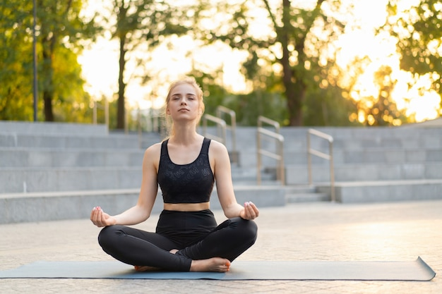 Yoga e meditazione in città moderna donna caucasica rilassarsi posizione del loto seduta tappetino yoga all'aperto parco estivo su pavimento di cemento giovane adulto femmina in forma rilassante dopo l'allenamento pratica yoga siddhasana